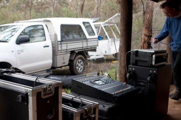 Engineer patching speakers deep in the bush